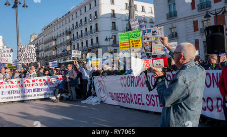 A protester seen chanting slogans on a megaphone before the protesters holding banners and placards during the demonstration. The unions protested at Puerta del Sol in Madrid against cuts in pensions gathering hundreds of people. - Stock Photo