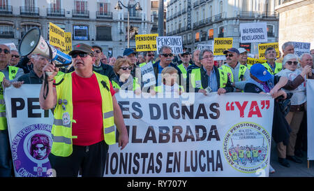 A protester seen chanting slogans on a megaphone before the protesters holding a banner and placards during the demonstration. The unions protested at Puerta del Sol in Madrid against cuts in pensions gathering hundreds of people. - Stock Photo