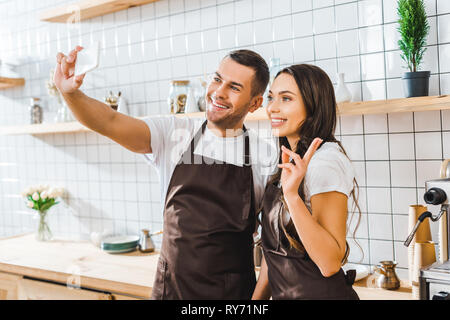 cashiers in aprons standing near bar counter and taking selfie in coffee house