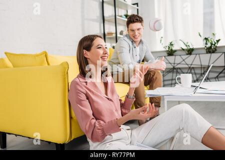 beautiful woman throwing in air baseball and sitting on floor near cheerful boyfriend sitting on sofa - Stock Photo