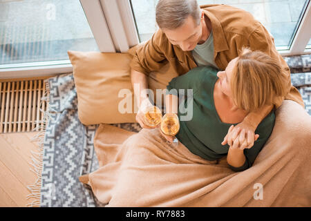 overhead view of couple sitting on floor by large window and clinking glasses of white wine - Stock Photo