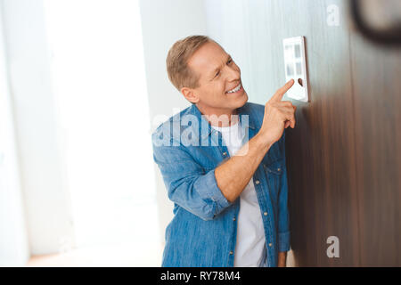 handsome smiling man using smart home control panel - Stock Photo