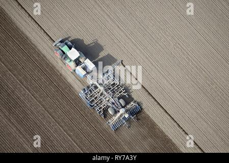 Modern agriculture, tractor working arable land in a field, Schleswig-Holstein, Germany - Stock Photo