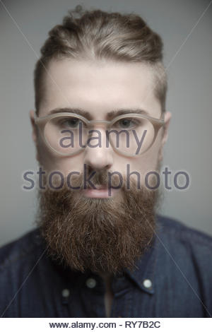 Close up portrait confident handsome young man with eyeglasses and beard - Stock Photo