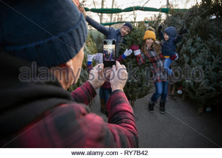 Worker with smart phone photographing happy family shopping for christmas tree at christmas market - Stock Photo