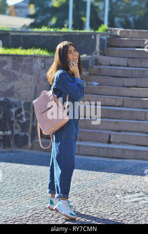 A young girl walks around the city with a pink backpack talking on the phone, dressed in a denim suit and light sneakers - Stock Photo