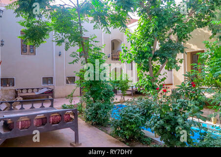 Yazd Old Town Residential House Courtyard Garden with Fountain Pool and Persian Sitting Table - Stock Photo