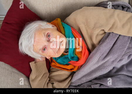 Close up picture of a sick old lady lying on the couch wrapped in a blanket, wearing colorful scarf - Stock Photo