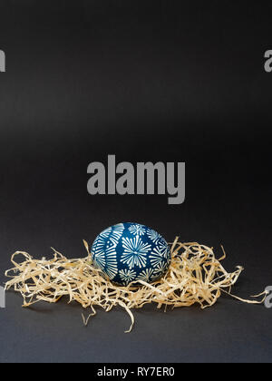 One traditional Easter egg, lithuanian is called margutis, natural painting  blue and white pattern with bees wax in the nest, on black background - Stock Photo