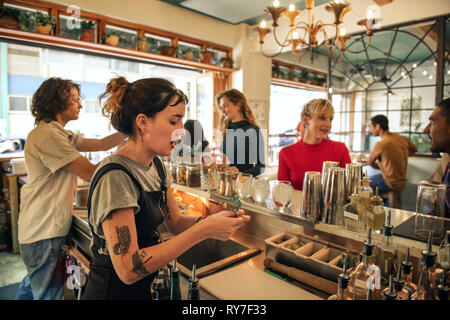 Young female bartender pouring cocktails behind a bar counter - Stock Photo