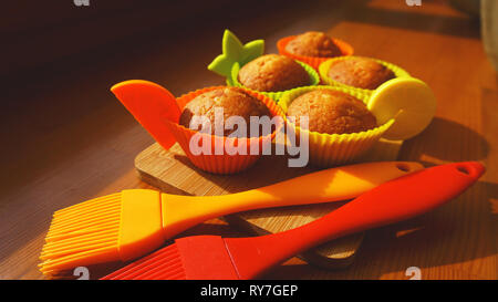 Simple mini muffins in colorful silicone bakeware. Silicone cup baking cupcakes and silicone brushes. Kitchen and cooking concept on wooden background - Stock Photo
