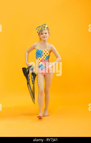 Girl wearing swimwear standing with snorkelers and flippers on yellow studio background. - Stock Photo