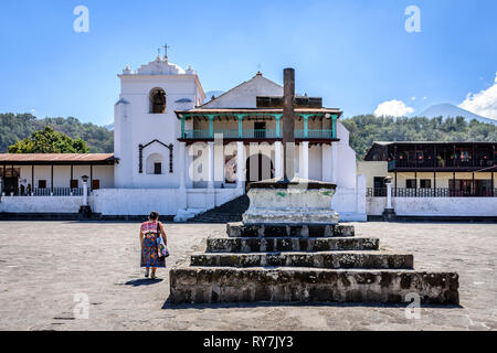 Santiago Atitlan, Lake Atitlan, Guatemala - March 8, 2019: Maya woman walks across plaza to Catholic church in lakeside town in Guatemalan highlands. - Stock Photo
