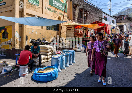 Santiago Atitlan, Lake Atitlan, Guatemala - March 8, 2019: Maya women walk past sacks of corn in Friday market in largest lakeside town. - Stock Photo