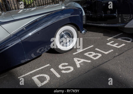 A 1964 Empress Bentley is parked in a Disabled bay in Smith Square, a small square behind the Houses of Parliament, before collecting its VIP passengers - barristers who are being sworn in as QCs (aka Silks in legal vernacular), on 11th March 2019, in London, England. - Stock Photo