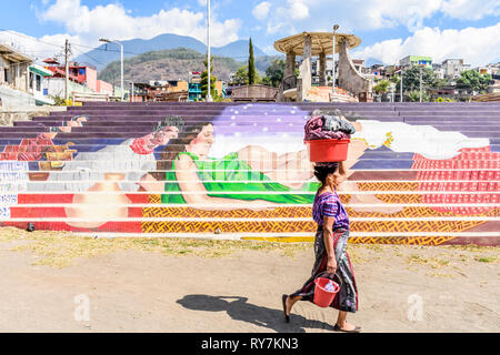 Santiago Atitlan, Lake Atitlan, Guatemala - March 8, 2019: Traditionally dressed Maya woman walks past colorful mural of childbirth in lakeside town - Stock Photo