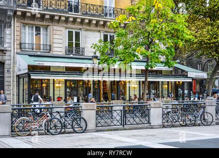 Bikes are parked in front of the Brasserie Les Deux Palais, a notable sidewalk cafe and Parisian restaurant on the Ile de la Cite in Paris France - Stock Photo