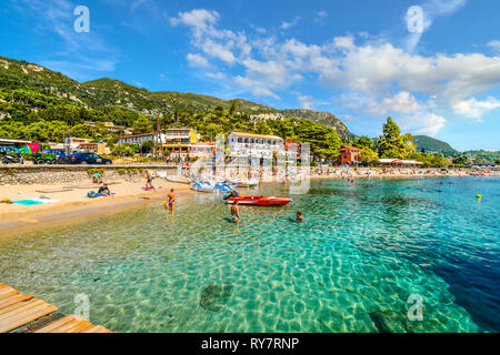 Tourists relax in the clear turquoise waters and on the sandy Palaiokastritsa beach on the Aegean island of Corfu, Greece. - Stock Photo