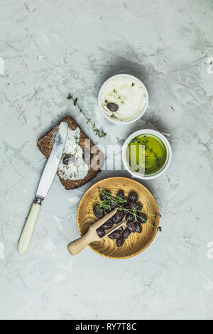 Whole wheat bread baked at home, bio ingredients, very healthy with seed, bowl of cream cheese and traditional greek italian appetizer dried olives on - Stock Photo
