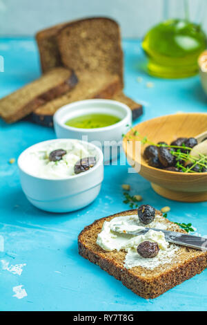 Cream Cheese on a slice of bread topped, bowl of cream cheese, mozzarella, pine nuts and traditional greek italian appetizer dried olives on blue conc - Stock Photo
