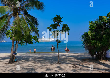 Tourists on Patong Beach, Phuket, Thailand, surrounded by greenery, with a large cruise ship anchored off shore - Stock Photo