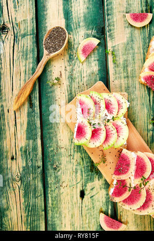 Healthy breakfast toasts from sliced watermelon radish or chinese daikon, chia and cottage cheese on board  on green wooden background. Top view. Flat - Stock Photo