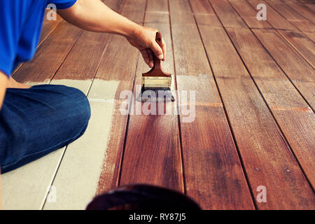 hand and painting brush paint brown color on wood floor ,diy concept - Stock Photo