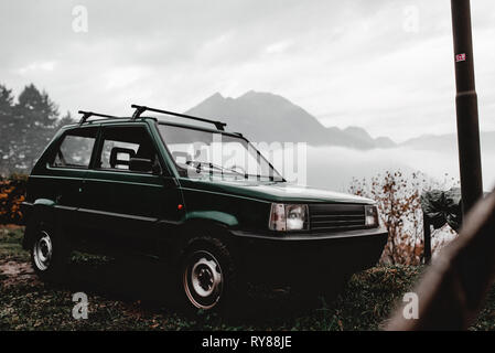 Vintage automobile parked on coast of lake near mountains in cloudy weather in Italy - Stock Photo