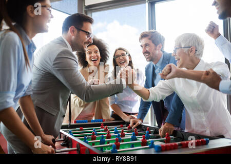 Business people having great time together.Colleagues playing table football in office. - Stock Photo