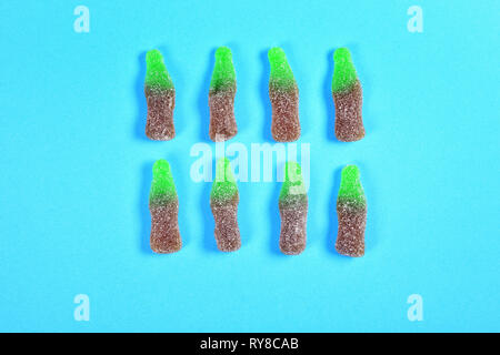 group of jelly candies coke bottles on blue background - Stock Photo