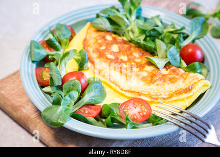 Homemade omelette with salad on plate. Healthy food concept. - Stock Photo