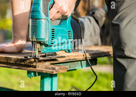 Employee working with electric jigsaw - Stock Photo