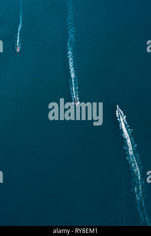 View from above, stunning aerial view of three long-tail boats with tourists on board sailing on a deep blue sea headed to Maya Bay, Phi Phi Islands.