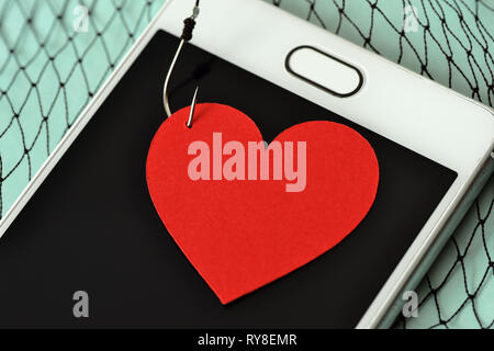 Heart on fish hook on mobile phone and fishing net - Love concept - Stock Photo
