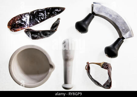 Flat lay featuring chilis and a pestle and mortar - Stock Photo