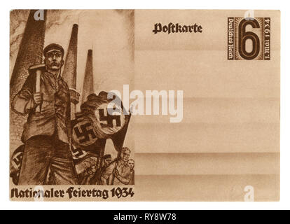 German historical postal card: National labor day, 1934, the worker heads the strike on the background of factory pipes and banners with swastika - Stock Photo