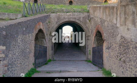 The entrance of the tunnel under the ampitheatre in Pompeii Italy with the opening going inside of the ruins - Stock Photo