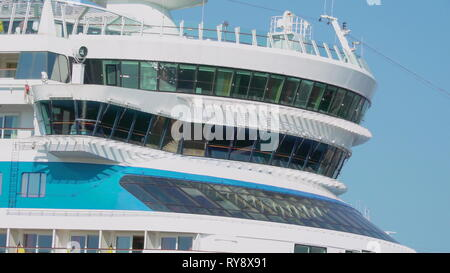 Small glass windows of the big white cruise ship docking on the port in the city - Stock Photo