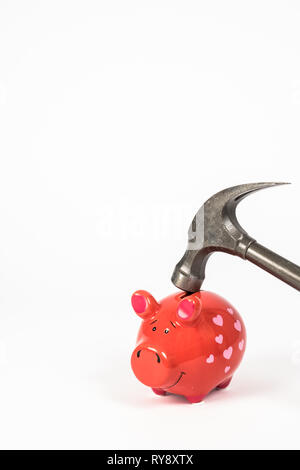 A hammer breaks a red piggy bank. White background and plenty of space for your own text / copy space. Vertical. - Stock Photo