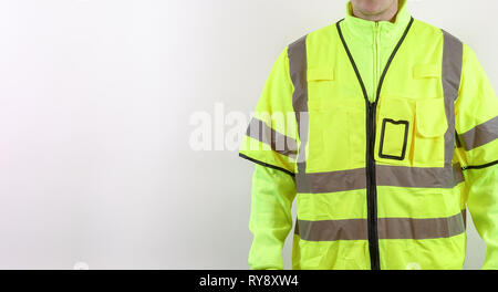 A man with warning safety clothes for roadworks and construction sites. High visibility reflective yellow safety vest. Plenty of copy space for your o - Stock Photo