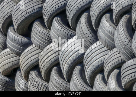 Old used tires that are lined up in a pile. - Stock Photo