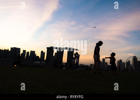 Mother talking to young son at Marina Barrage, with Singapore Sunset Skyline - Stock Photo