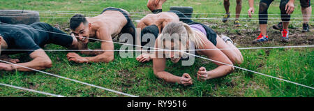Participants in an obstacle course crawling - Stock Photo