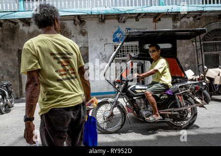 An elderly Filipino man watches a tricycle driver pass by on the street - Romblon City, Philippines - Stock Photo