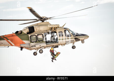 Rescue helicopter in flight winching rescuer. - Stock Photo