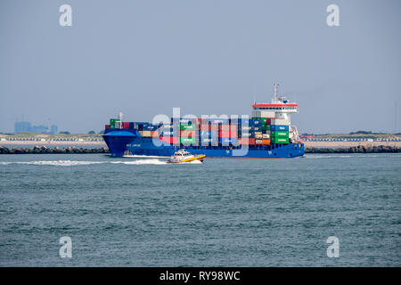 Small pilot boat passes sea going container ship - Stock Photo
