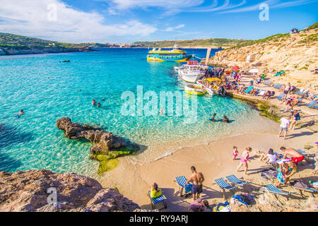 Comino, Malta - November, 2018: Tourists crowd at Blue Lagoon to enjoy the clear turquoise water on a sunny summer day with clear blue sky and boats - Stock Photo