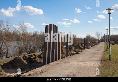Row of steel pillar hitting in the ground to stabilizes the flood protection dam - Stock Photo