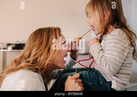 Woman doctor examining throat of little girl with spatula. Pediatrician checking throat of a girl child. - Stock Photo