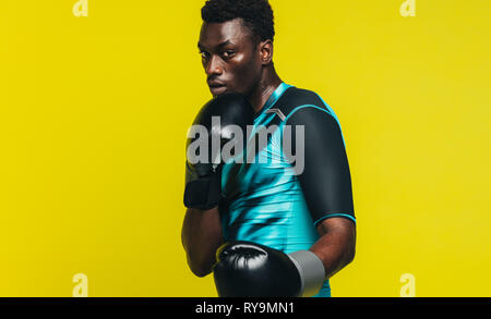 African man in boxing stance over yellow background. Man in sportswear wearing boxing gloves practicing his moves. - Stock Photo